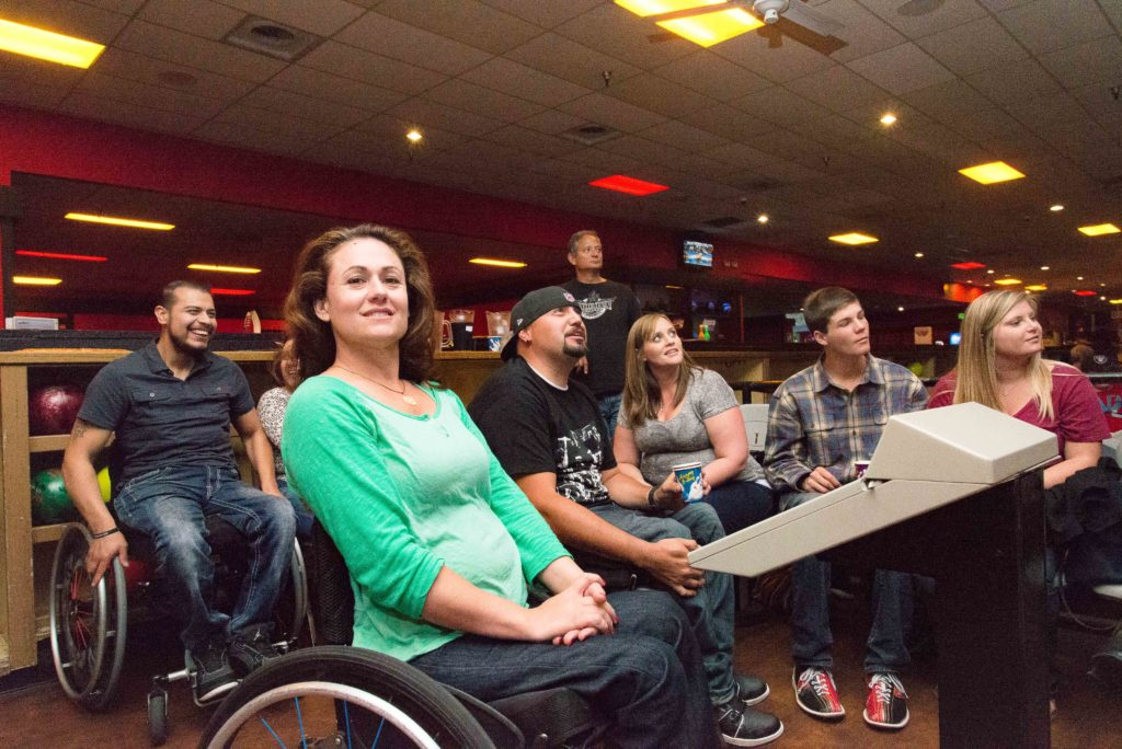Smiling wheelchair user Lake Kowell in midground. Behind her are 7 people-mixed wheelchair users and not. Bowling balls and shoes can be seen.