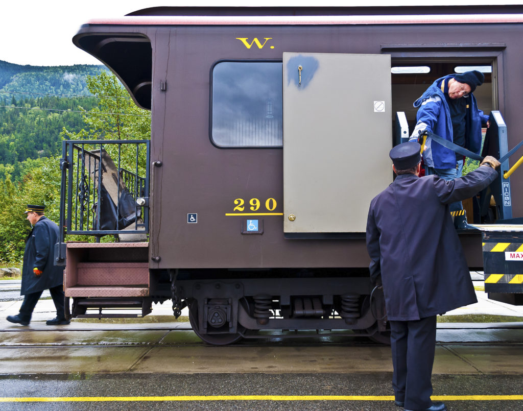 Depicted is an older railroad car with two accessibility symbols. A man with his head strongly tilted to the side is standing on a lift to go from the train to the ground. A uniformed person is assisting.