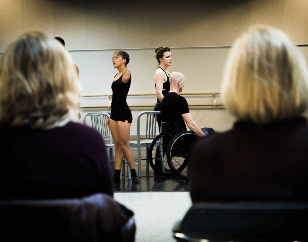 Three dancers form the Axis Dance Company pause mid performance. The bald headed guy is using a wheelchair and another dancer is missing her left arm. There are two audience members in the foreground framing the shot.